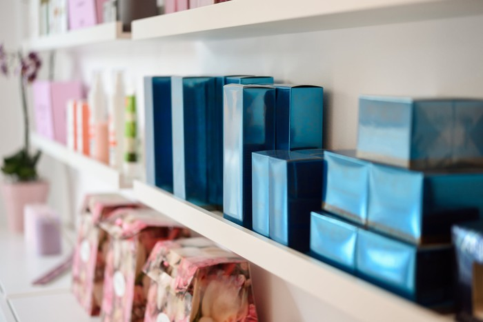 Boxes of luxury perfumes and skincare products line the shelves of a shop.