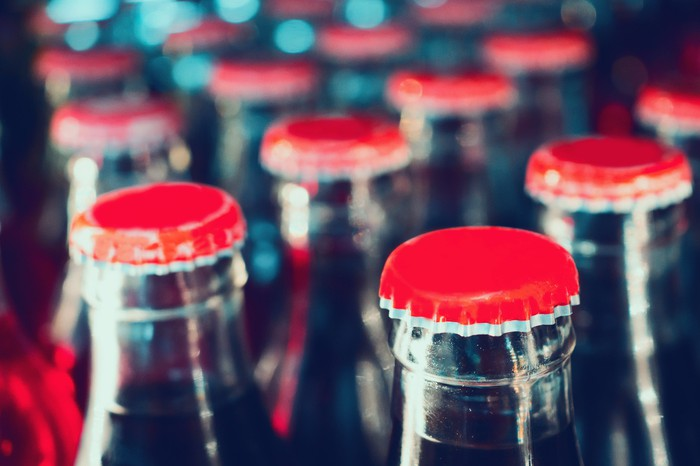 Close-up of glass soda bottles in a bottling plant.