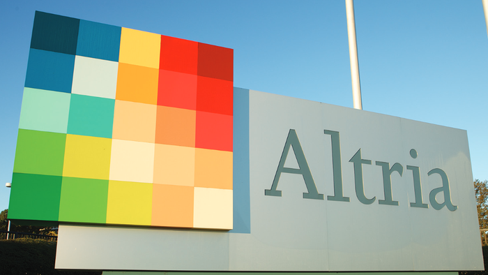 Altria sign with multicolored logo and flagpole in background.