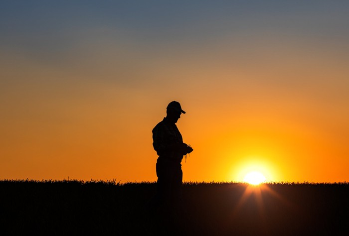 The silhouette of a farmer in the fields as sun goes down.