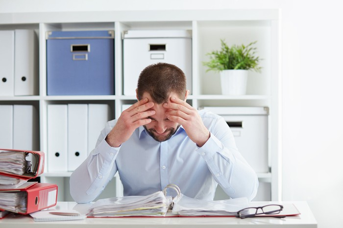 A man seated at a desk looks down at an open binder as if in frustration, hands on head.