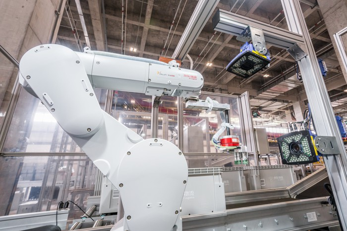 A large robot arm picks items for packing at a JD.com warehouse in Shanghai.
