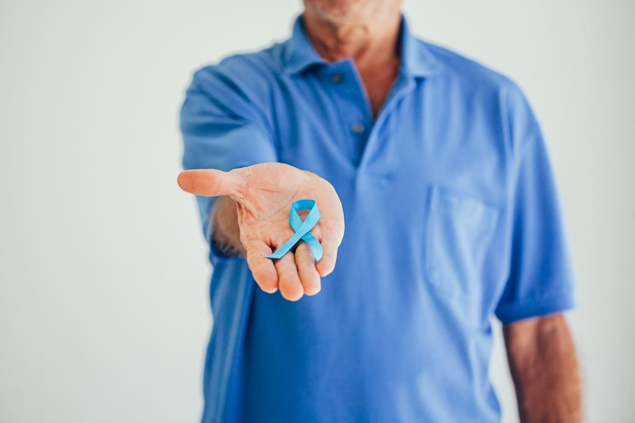 A man holding a prostate cancer ribbon in his palm.
