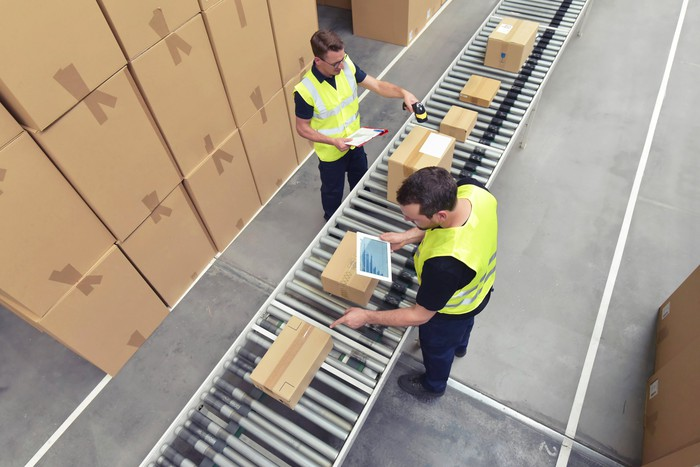 Shipping company employees working on a package conveyor system.