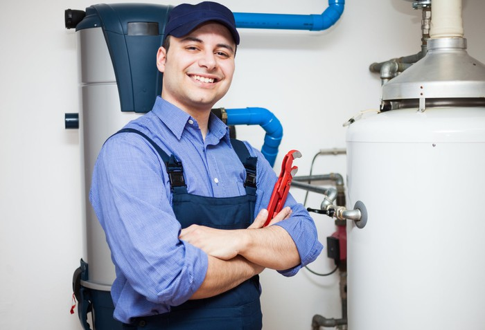A smiling man holding a wrench stands next to a water heater