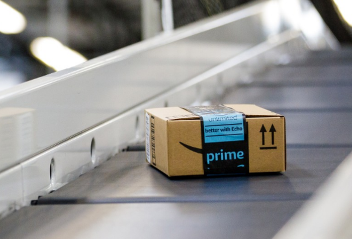 An Amazon box traveling on a conveyor belt in a fulfillment center.