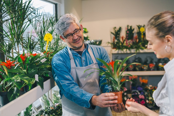 Older man in flower shop handing plant to woman