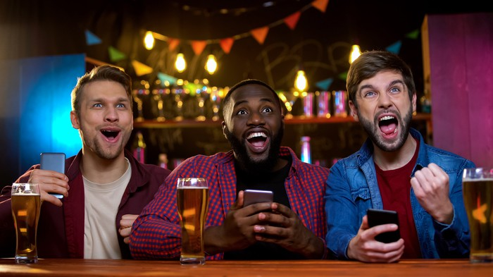 Three men in a bar watching sports on tv, phones in hand, and cheering.