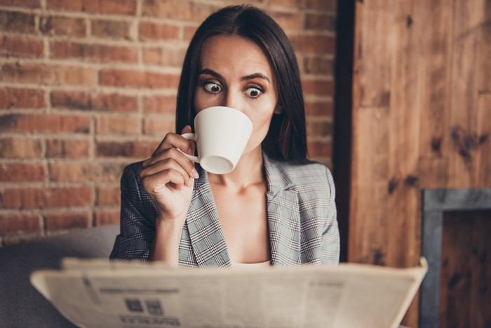 A woman in professional attire looks surprised as she drinks from a cup and reads a newspaper.