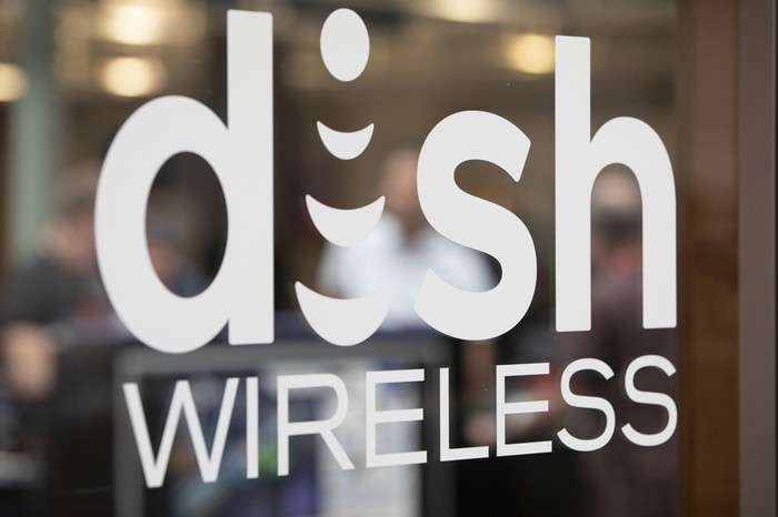 the DISH Wireless logo is painted on a piece of glass outside a store