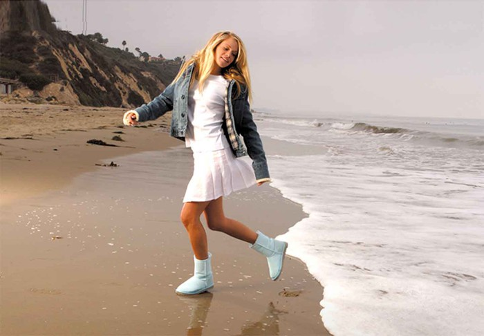 A woman on a beach wearing a white dress, a jeans jacket, and white UGGs