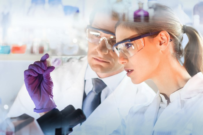 A man and woman in lab coats and protective goggles looking at a microscope slide.