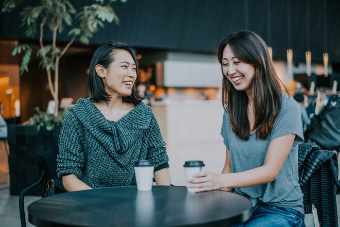 Two Asian women enjoying a cup of coffee.