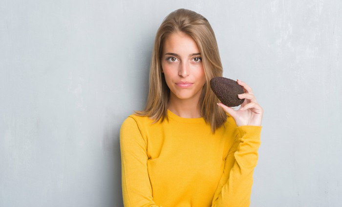 Young woman holds an avocado.
