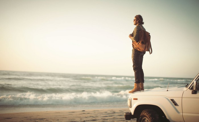 A person in Uggs standing on the hood of a car that's parked at the beach.