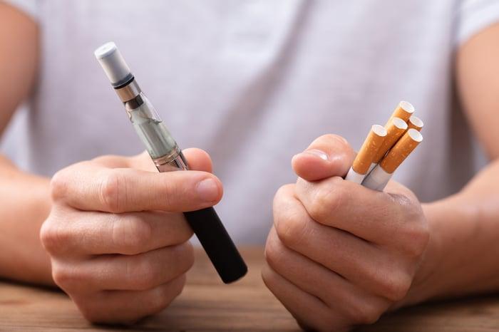 Picture of man holding cigarettes and E-cigarette