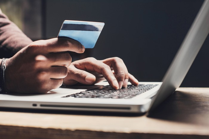 A person holds a credit card in one hand and types on a laptop with the other