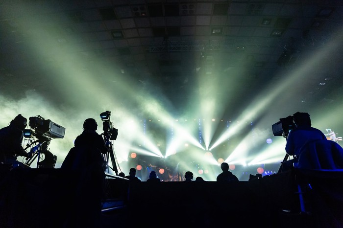 Silhouetted cameramen at a concert