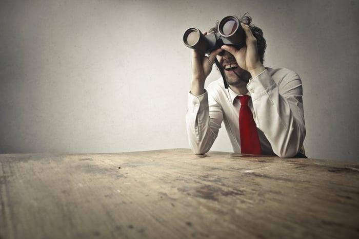 A businessman looking through giant binoculars.