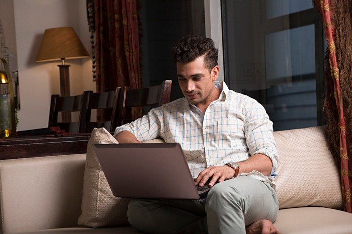 Young man on couch typing on laptop