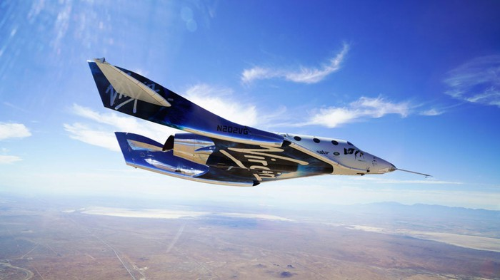 Virgin Galactic spacecraft flying over a desert.