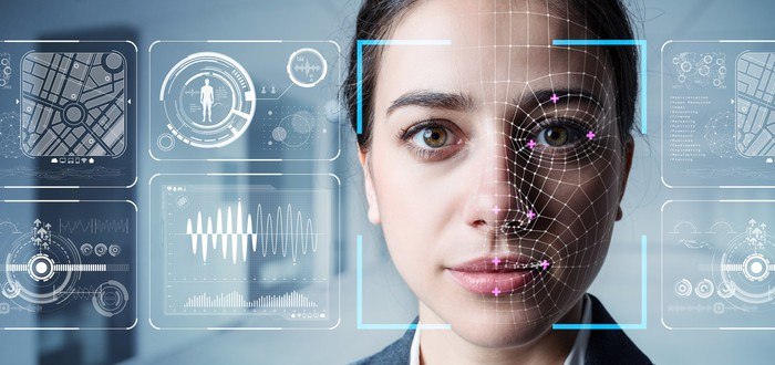 Young woman looks into the camera as computer-generated augmented reality graphics animate her face and the space around it.
