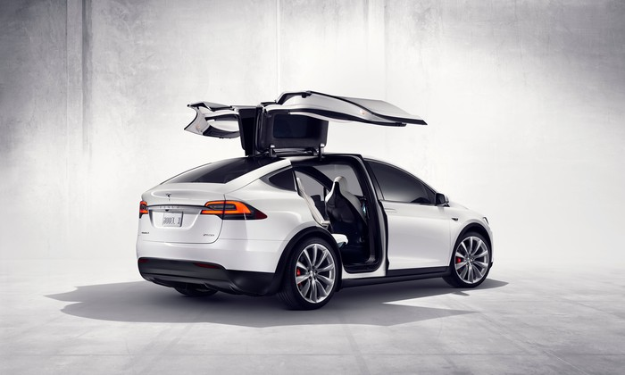 A white Tesla Model X with the falcon wing doors raised.