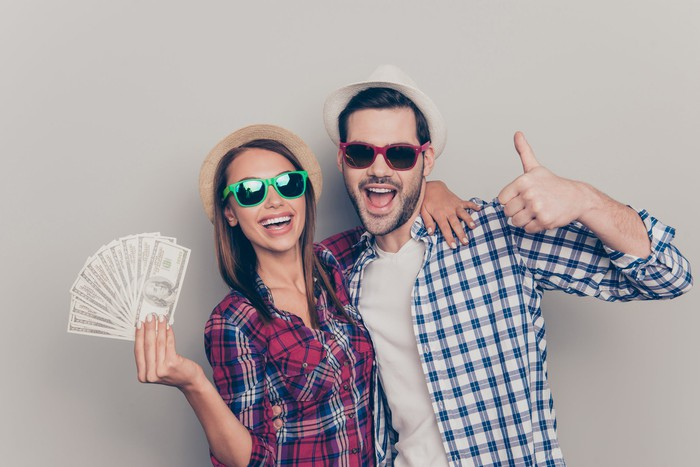 Smiling young woman fanning out stack of hundred-dollar bills while putting arm around smiling young man