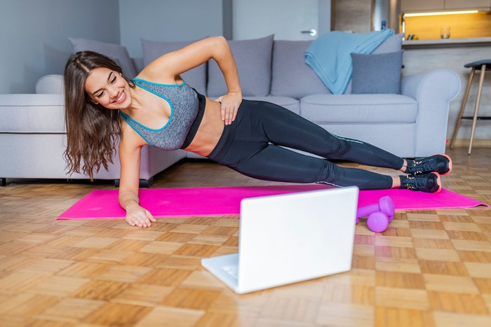 A woman doing strength exercises while looking at a laptop sitting on the floor.