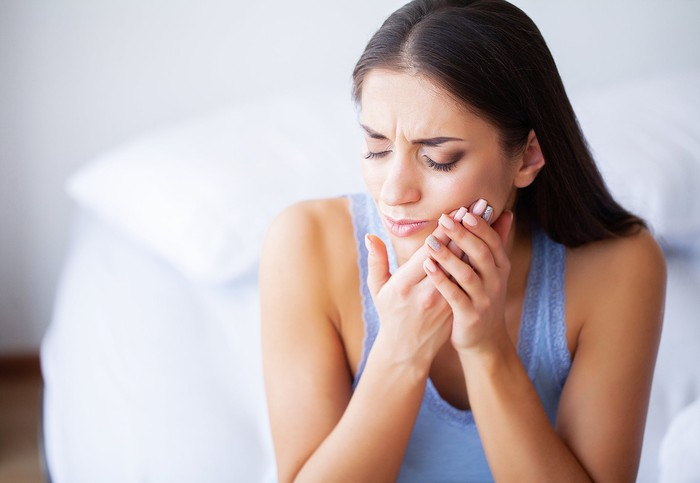 Woman holding the side of her mouth as if in pain