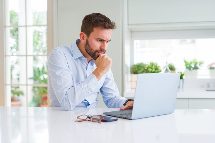 Man with serious expression resting chin on hand while looking at laptop.