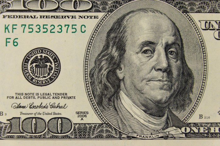 A U.S. hundred dollar bill showing Franklin portrait and other information.