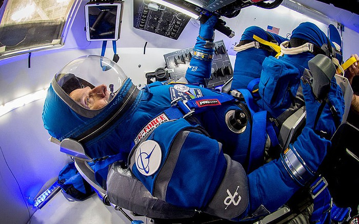 Astronaut in spacesuit within a Starliner space capsule