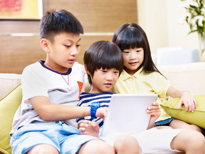 Three young children sitting on a couch, looking at a tablet