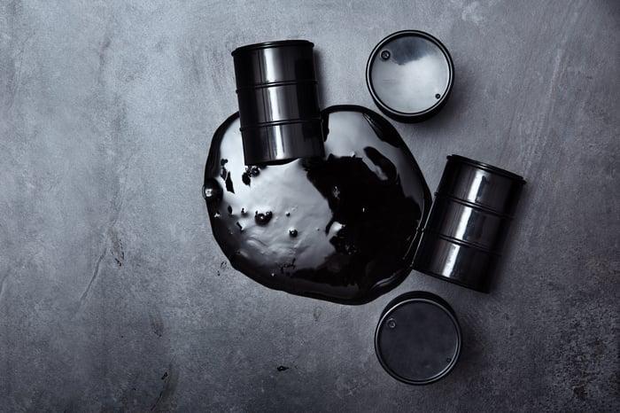 An oil barrel spills black liquid onto the floor