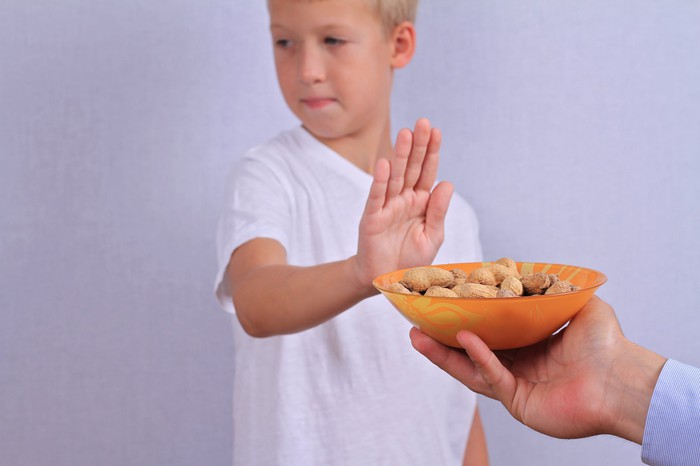 Boy holding up hand to bowl of peanuts.