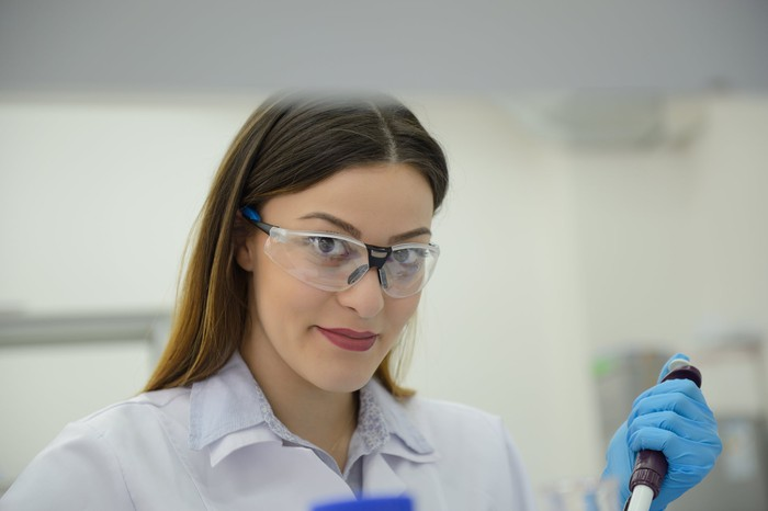 A lab researcher wearing protective eye-wear and using a pipette.