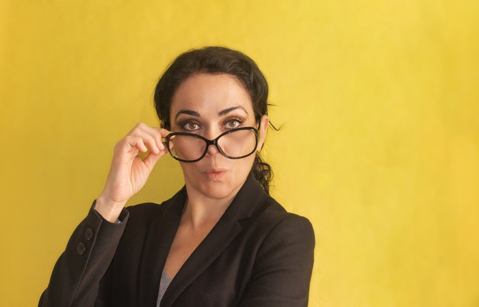 A professionally dressed woman peers over the top of her glasses with a look of surprise.