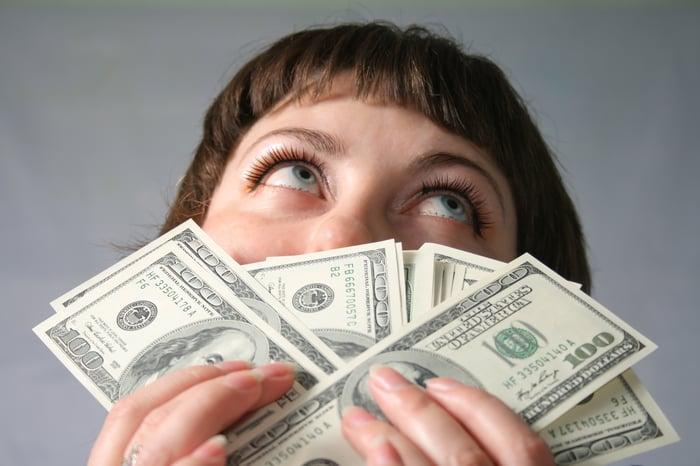 Woman holding several one hundred dollar bills