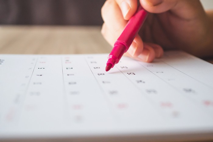 A person with a red pen about to circle a date on a calendar.