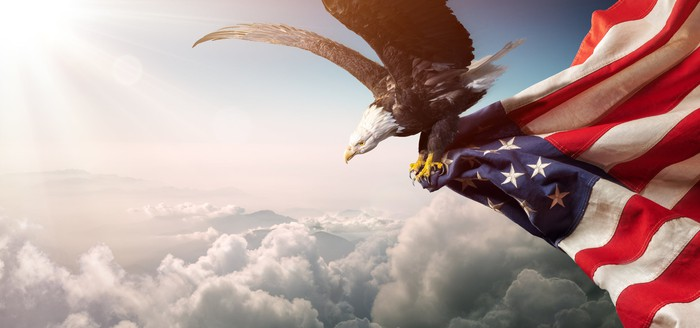 A bald eagle carries an American flag in its claws as it soars through the clouds.