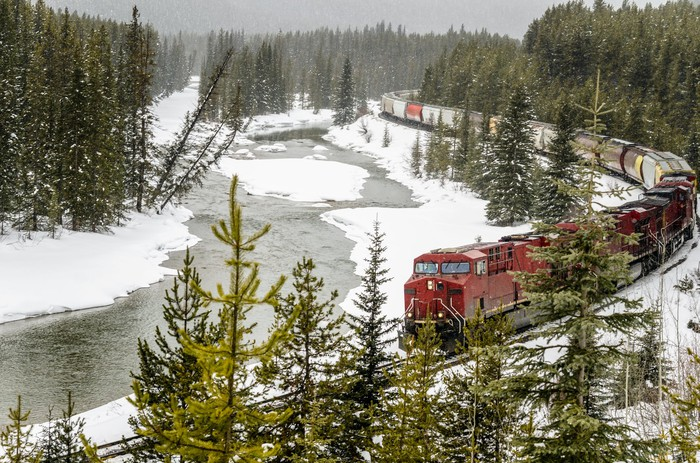 A freight train traveling through a snowy landscape