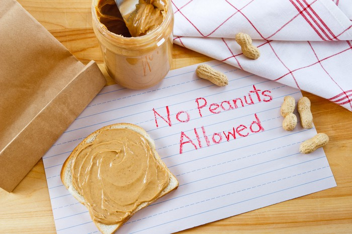 No Peanuts Allowed is written in red crayon on a piece of paper, next to a slice of bread spread with peanut butter and a jar of peanut butter.