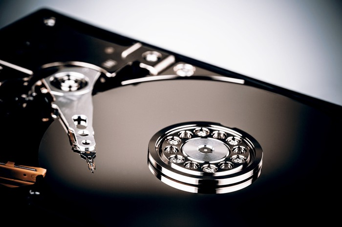 Close-up shot in dramatic lighting of a hard drive with the top cover removed.