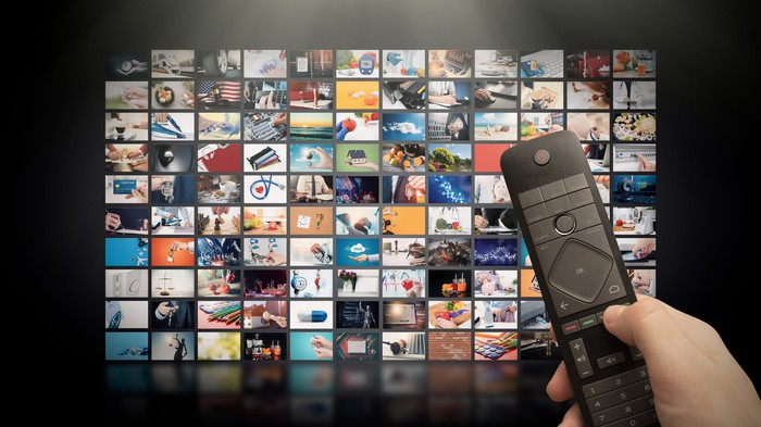 A hand holding a TV remote with a collage of content options in the background.