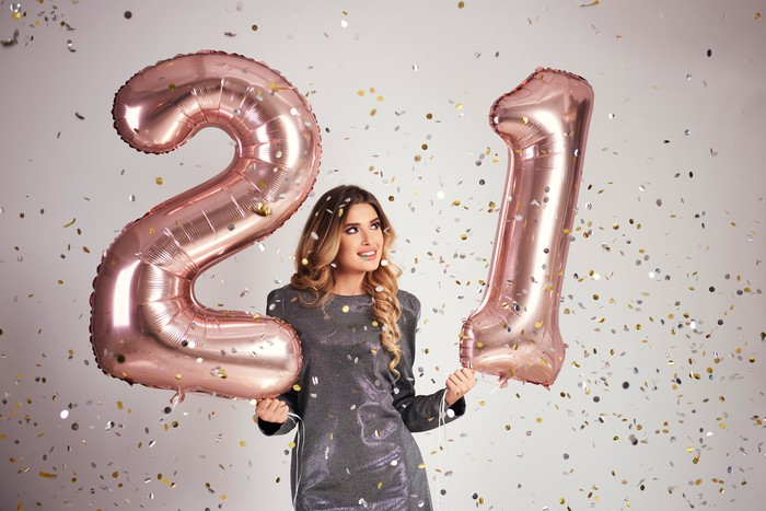 Young woman holding balloon numbers 21