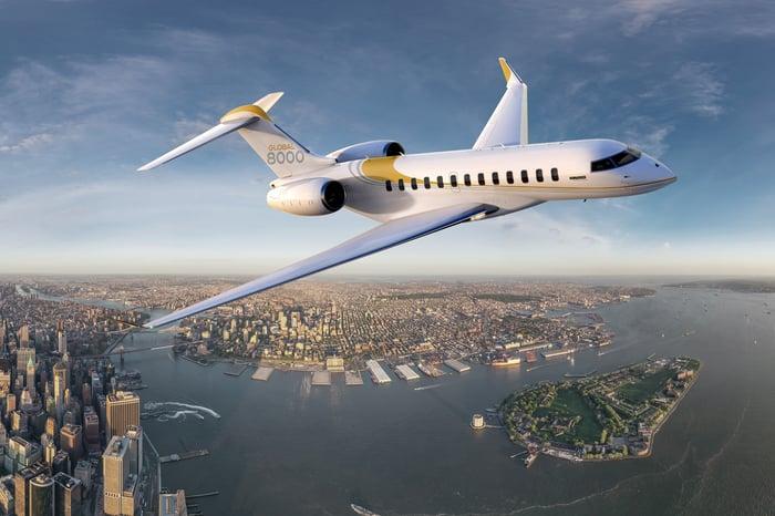 The Global 8000 flies over a metropolitan skyline.