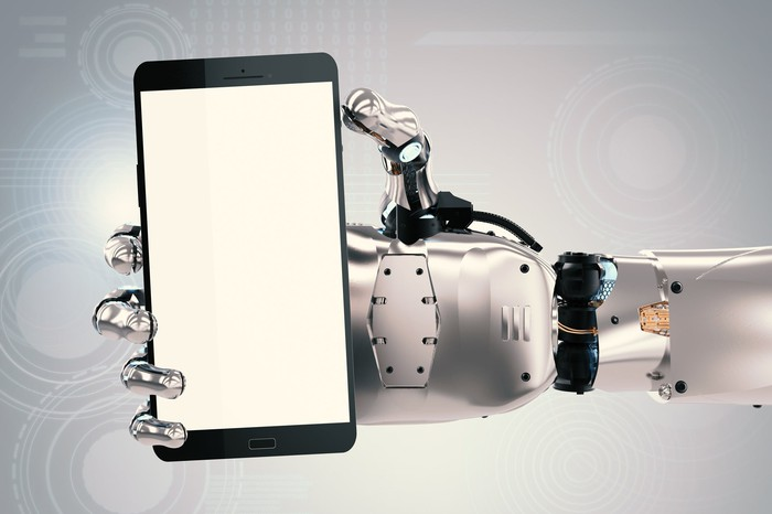 A robotic hand holds a smartphone.