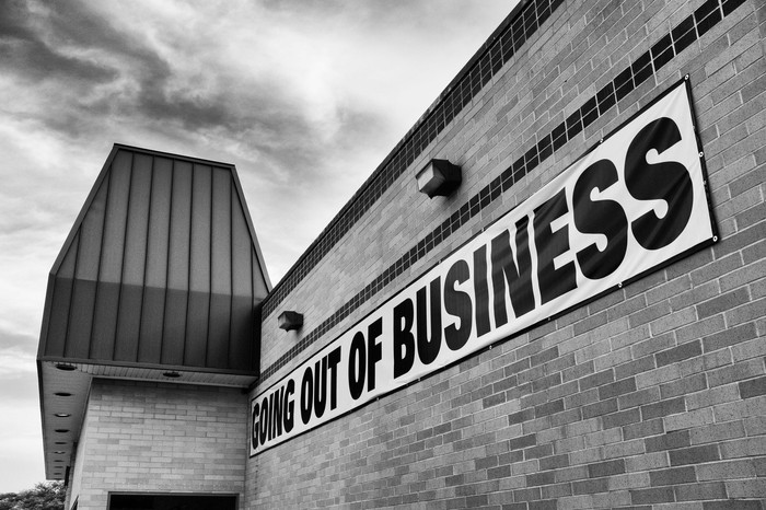 Going out of business banner on a brick store wall in black and white