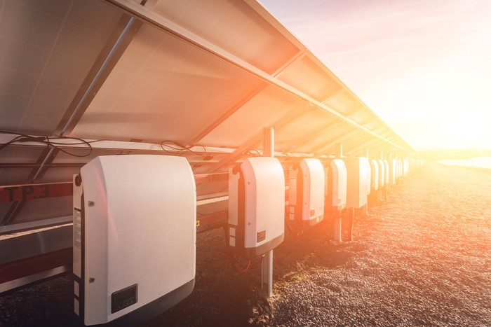 Solar inverters behind a row of solar panels in bright sunshine